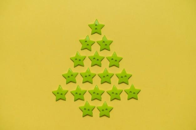 Kerstboom gemaakt van groene knopen in de vorm van sterren op een gele achtergrond. nieuwjaar en kerstconcept