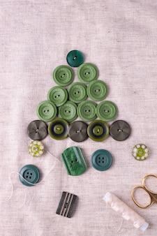 Kerstboom gemaakt van groene knopen op linnen stof. stap 2.