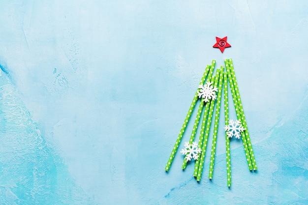 Kerstboom gemaakt van het drinken van kleurrijk papier en sneeuwvlokken speelgoed op blauwe ondergrond. nieuwjaar concept.