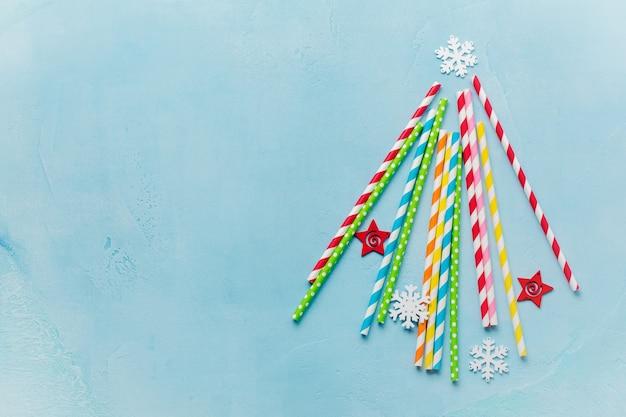 Kerstboom gemaakt van het drinken van kleurrijk papier en sneeuwvlokken speelgoed op blauwe ondergrond.