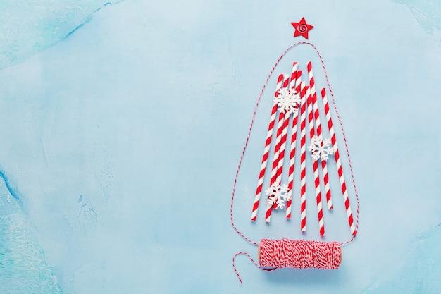 Kerstboom gemaakt van het drinken van kleurrijk papier met witte marshmallows en sneeuwvlokken speelgoed op blauwe ondergrond. nieuwjaar concept. Premium Foto
