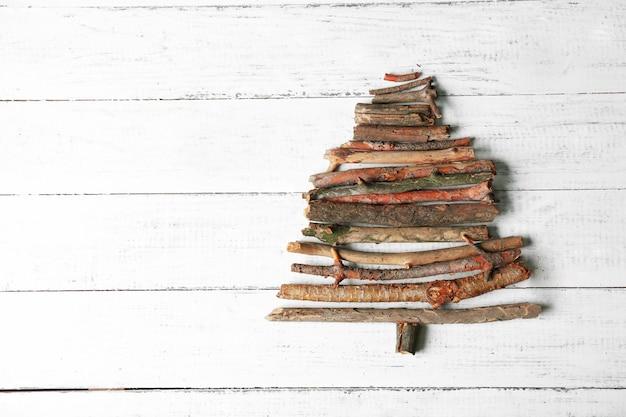 Kerstboom gemaakt van houten takken op houten tafelblad weergave