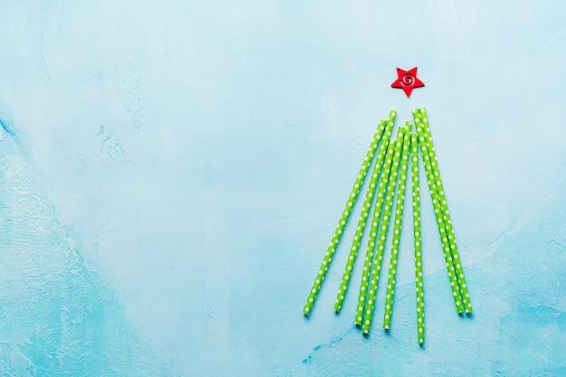 Kerstboom gemaakt van kleurrijke papier drinken op blauwe ondergrond. nieuwjaar concept.