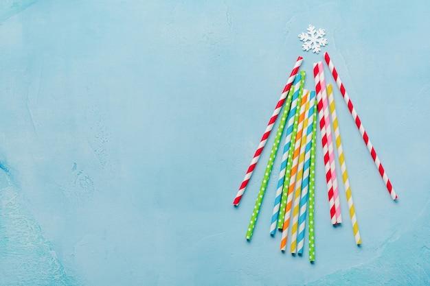 Kerstboom gemaakt van kleurrijke papier drinken op blauwe ondergrond