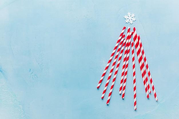 Kerstboom gemaakt van kleurrijke papier drinken op blauwe ondergrond.