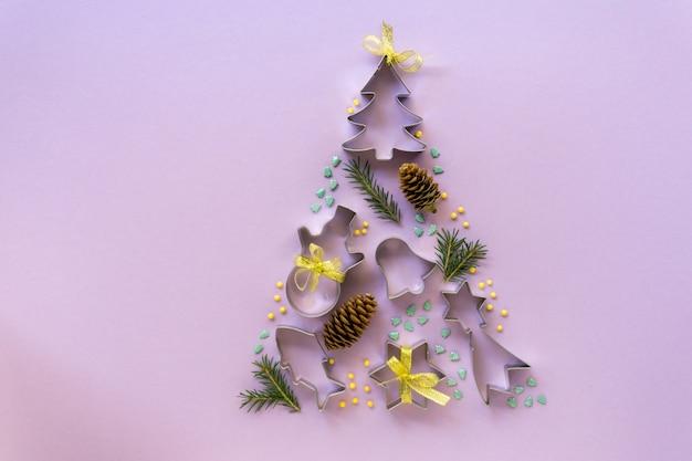 Kerstboom gemaakt van koekjessnijders, zoete hagelslag en kegels op lila achtergrond. nieuwjaar plat lag, ruimte voor tekst.