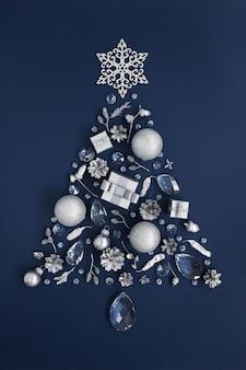 Kerstboom gemaakt van kristallen en zilveren nieuwjaarsversieringen op donkerblauw