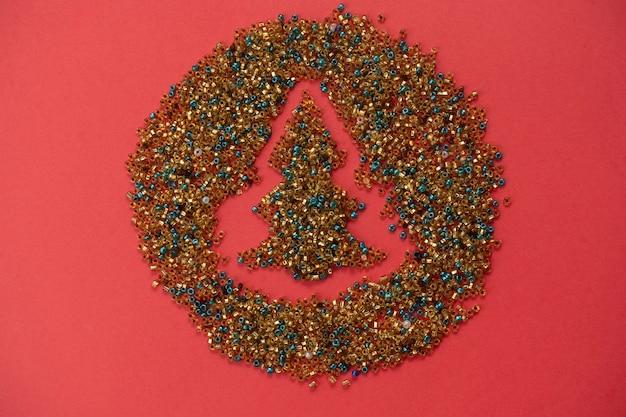 Kerstboom gemaakt van mini kralen ornament op rode achtergrond. kerstmis een nieuwjaar concept. bovenaanzicht, plat lag. selectieve aandacht.