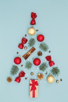 Kerstboom gemaakt van nieuwjaars versieringen op blauwe ondergrond