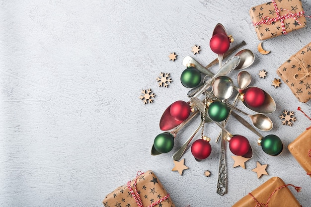 Kerstboom gemaakt van oude lepels of bestek met rode en groene kerstballen en geschenkdozen op grijze steen of betonnen ondergrond. bovenaanzicht met kopie ruimte.