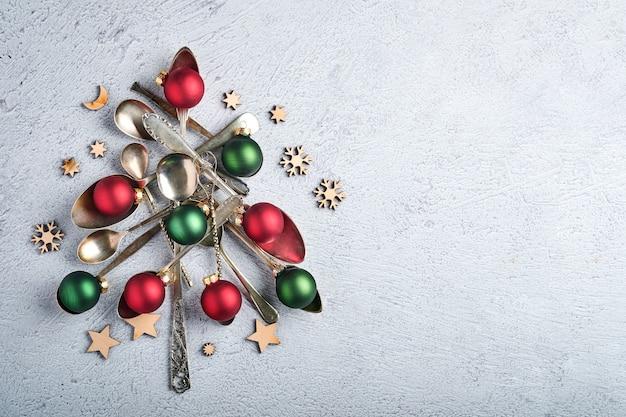 Kerstboom gemaakt van oude lepels of bestek met rode en groene kerstballen op grijze steen of betonnen ondergrond. bovenaanzicht met kopie ruimte.