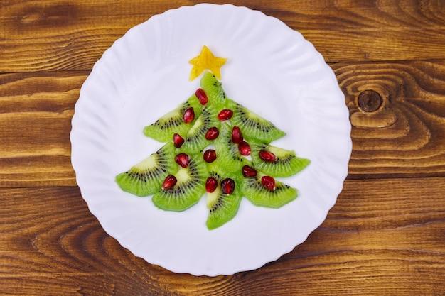 Kerstboom gemaakt van plakjes kiwi en granaatappel op houten tafel. bovenaanzicht. creatief idee voor feestelijke desserts voor kerstmis en nieuwjaar. grappig voedselidee voor kinderen