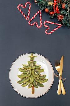 Kerstboom gemaakt van plakjes kiwi op een witte plaat en kerstversiering op tafel
