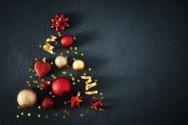 Kerstboom gemaakt van rode en gouden kerstballen en feestelijke linten Premium Foto