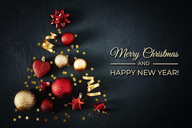 Kerstboom gemaakt van rode en gouden kerstballen en feestelijke linten