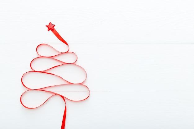 Kerstboom gemaakt van rood satijnen lint met ster erop