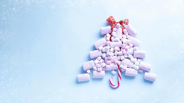 Kerstboom gemaakt van roze marshmallows en snoepgoed afbeelding met kopieerruimte en sneeuweffect
