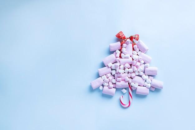 Kerstboom gemaakt van roze marshmallows en snoepgoed op lichtblauwe achtergrond