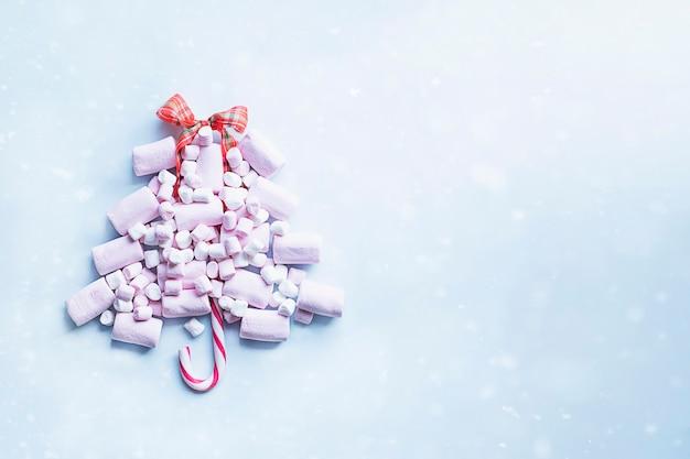 Kerstboom gemaakt van roze marshmallows en snoepriet met sneeuweffect