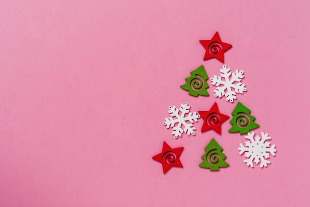 Kerstboom gemaakt van speelgoed en sneeuwvlokken liggend op een roze oppervlakteachtergrond. nieuwjaar of kerstmis concept. bovenaanzicht. omgaan met ruimte.