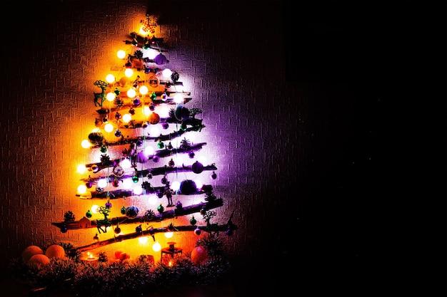 Kerstboom gemaakt van stokken met paars oranje lichten