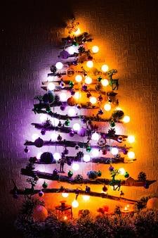Kerstboom gemaakt van twijgen en stokken met paarse en oranje lichten 's nachts.