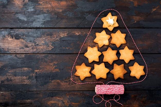Kerstboom gemaakt van zelfgemaakte peperkoekkoekjes op oude rustieke houten tafel. bovenaanzicht.