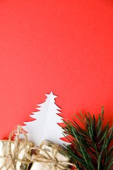 Kerstboom gesneden uit papier, pijnboomtak en twee dozen