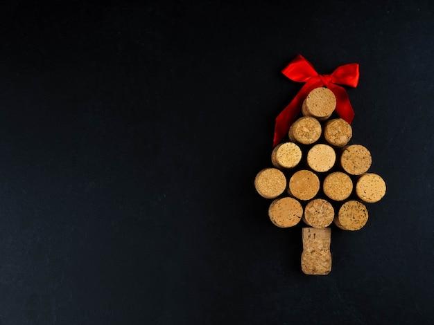 Kerstboom gevormd door kurken op zwarte achtergrond, met roze en rode linten concept kerstmis, copyspace, plat lag