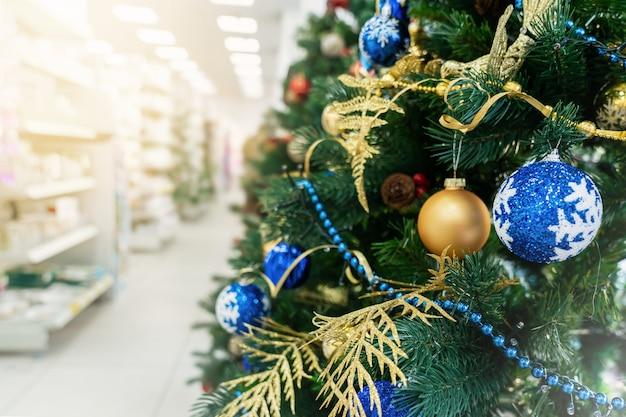 Kerstboom in de winkel, versierd met ballonnen, winkelen en verkopen voor het nieuwe jaar