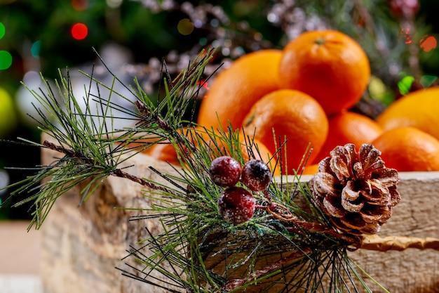 Kerstboom in een pot op sinaasappelen en dozen met geschenken.