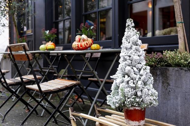 Kerstboom in sneeuw in straatcafé. nieuwjaar en kerstmis in europese vintage retrostijl in de buurt van buitentafels met stoelen op caféterras. kerstmarkt straatvoedsel.