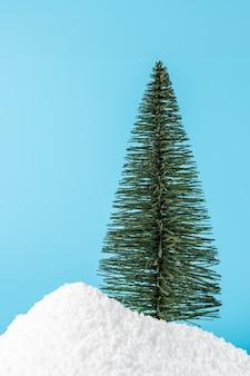 Kerstboom in sneeuw op blauw