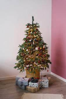 Kerstboom in verlichting met speelgoed en geschenken eronder in het interieur van de woonkamer