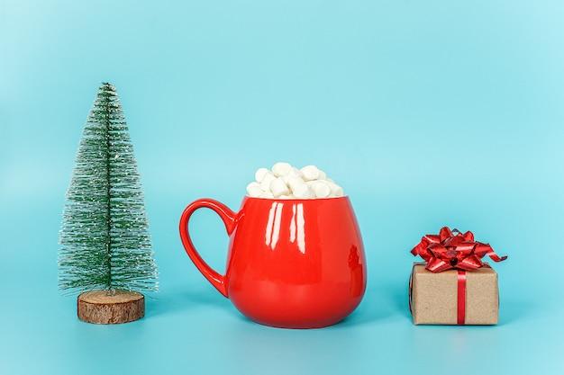 Kerstboom, kopje marshmallow en geschenkdoos op blauwe muur. prettige kerstdagen of gelukkig nieuwjaar concept.