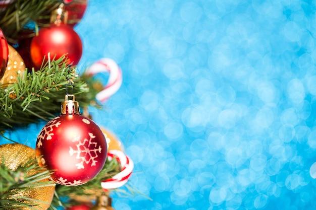Kerstboom met ballen en snoepjes op blauw glitter oppervlak