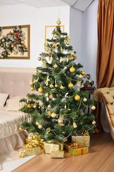 Kerstboom met balspeelgoed en geschenkdoos presenteert eronder in de woonkamer