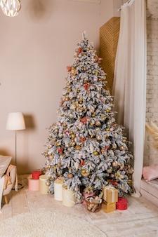 Kerstboom met cadeautjes. vakantie decoratie. elegante kerstboom met wit en roze speelgoed in de luxe appartementen. grote prachtig versierde boom met roze kerstballen, linten, sneeuwvlokken