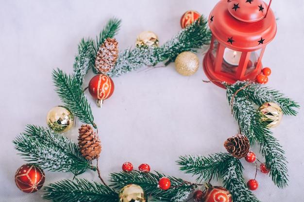 Kerstboom met decoratie en lamp op een witte tafel.