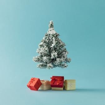 Kerstboom met geschenkdozen op helder blauw oppervlak