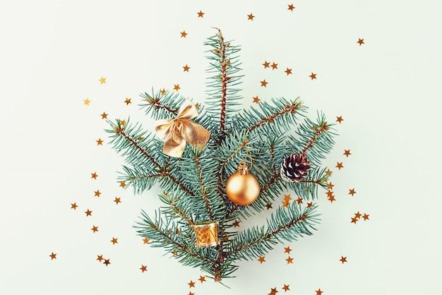 Kerstboom met gouden ballen en kerstmisspeelgoed wordt verfraaid op witte achtergrond die