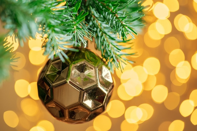 Kerstboom met gouden snuisterij bij bokeh het fonkelen