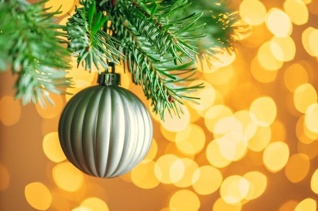 Kerstboom met grijze snuisterij bij het gouden bokeh fonkelen