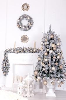 Kerstboom met kerstballen in de buurt van ingerichte open haard