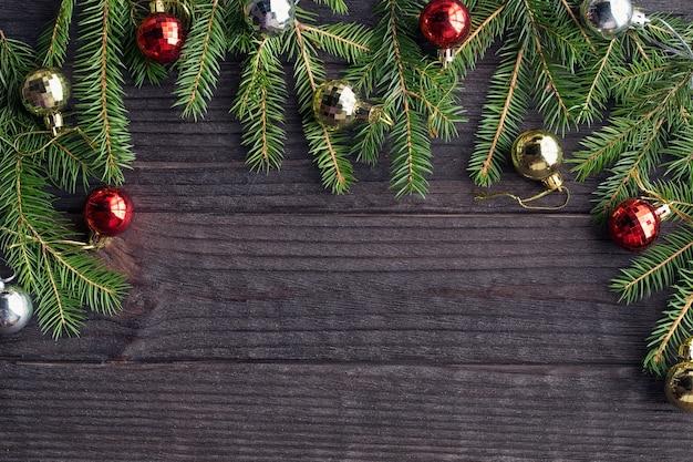 Kerstboom met kerstballen op houtstructuur.