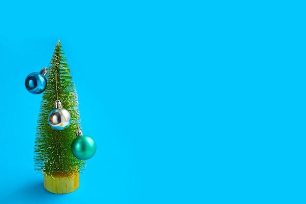 Kerstboom met kleine versieringen op blauw, abstract, minimalistisch kerstconcept