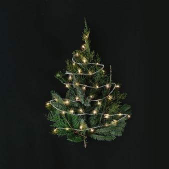 Kerstboom met lampjes op donkere tafelblad.