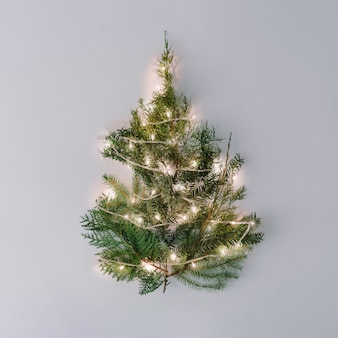 Kerstboom met lampjes op pastel grijs tafelblad.