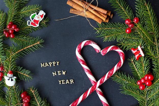 Kerstboom met ornamenten en snoep op een zwarte achtergrond. het opschrift gelukkig nieuwjaar