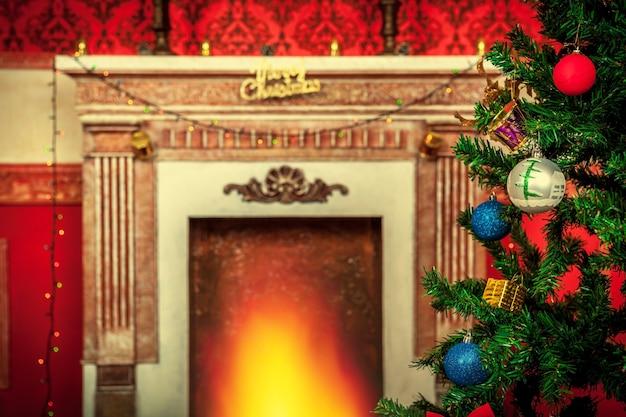 Kerstboom met ornamenten op de achtergrond van een open haard